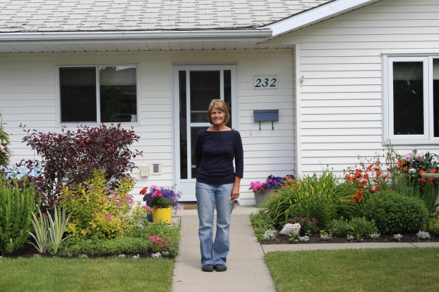 Judy in front of her house (supervising the move)