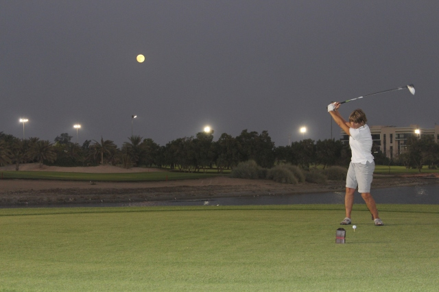 Judy teeing off on the 20th hole with full moon behind
